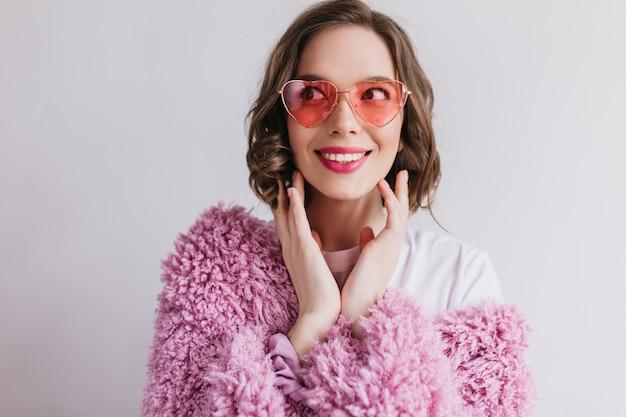 Gelukkig europees meisje in grappige zonnebril geïsoleerd op een witte muur. betoverende krullende vrouw in roze pluizig jasje positieve emoties uitdrukken.