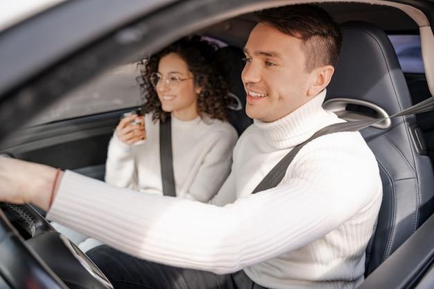 Gelukkig europees paar rijden in persoonlijke auto. jonge mooie krullende vrouw in glazen en volwassen man lacht. concept van auto rijden