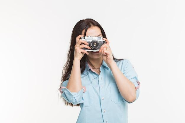 Gelukkig europees vrouwelijk model met donker haar dat binnen fotoshoot geniet. de jonge vrouw neemt een foto op witte muur.