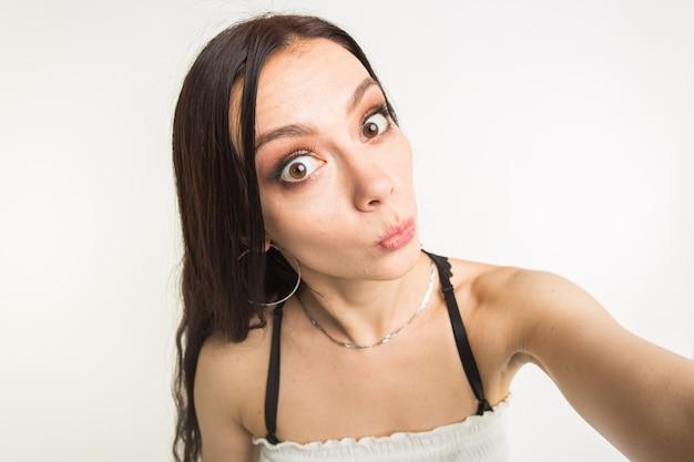 Gelukkig europees vrouwelijk model met donker haar genieten van indoor fotoshoot. jonge vrouw neemt een selfie op een witte achtergrond.