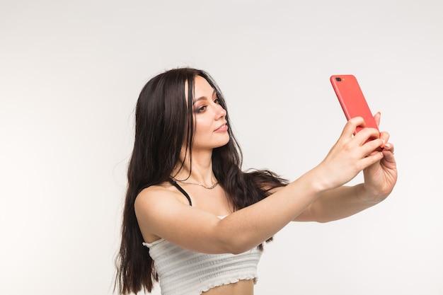 Gelukkig europees vrouwelijk model met donker haar genieten van indoor fotoshoot jonge vrouw neemt een selfie