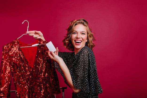 Gelukkig europees vrouwelijk model vond goedkope rode glitterjurk voor feest