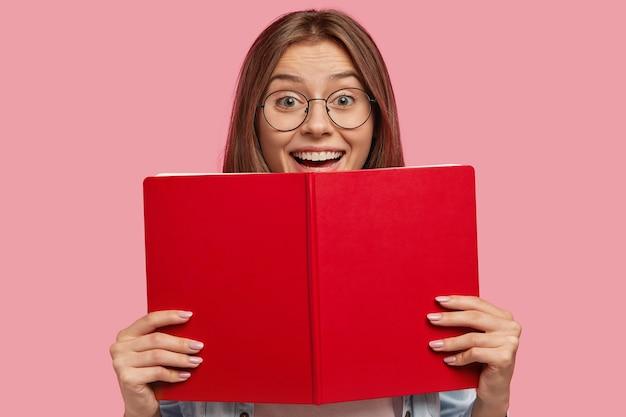 Gelukkig europese vrouwelijke student met bril, heeft positieve uitdrukking, houdt rood boek vast, verheugt zich met succes geslaagd voor examen aan de universiteit, geïsoleerd over roze muur. mensen, leren, lezen