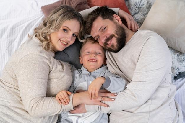 Gelukkig familieconcept moeder, vader en zoontje hebben plezier thuis kaukasische familie binnenshuis zwangere moeder baard vader en grappige kleine jongen liggen op de bank