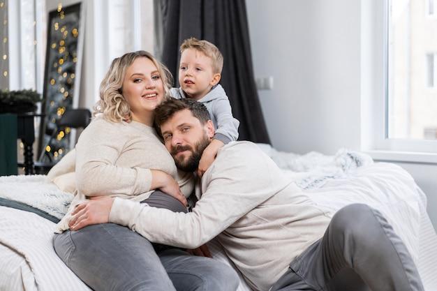 Gelukkig familieconcept moeder vader en zoontje hebben plezier thuis kaukasische familie binnenshuis zwangere moeder baard vader en grappige kleine jongen