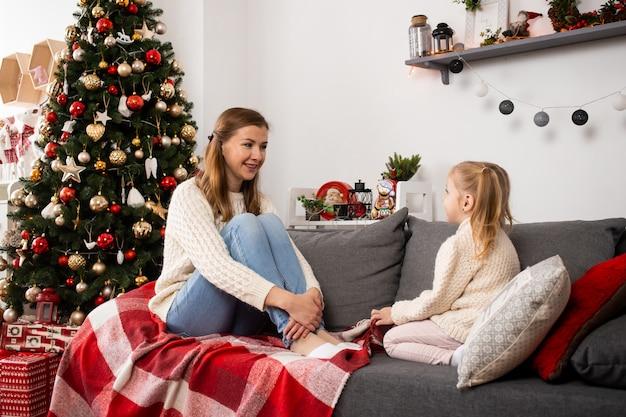 Gelukkig familiemoeder en kindmeisje dichtbij een kerstboom thuis