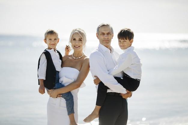 Gelukkig familieportret op de zonnige dag met twee tienerzonen die op de handen van de ouders zitten