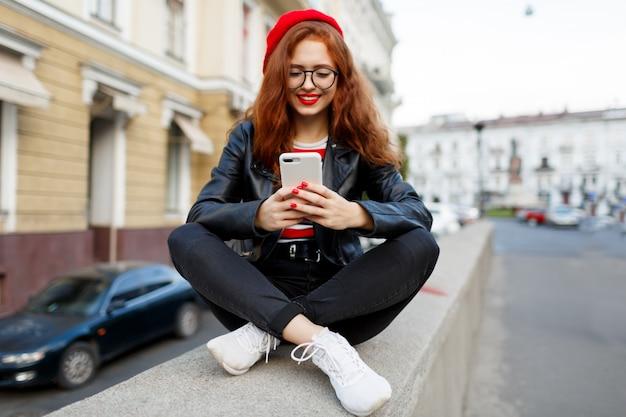 Gelukkig fantastische gember vrouw in stijlvolle rode baret in de straat met smartphone