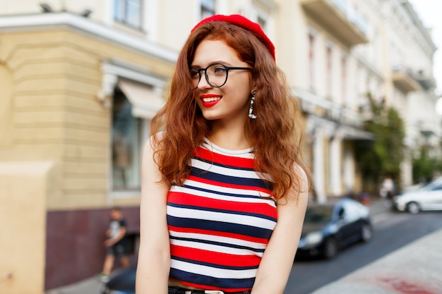 Gelukkig fantastische gember vrouw in stijlvolle rode baret in de straat