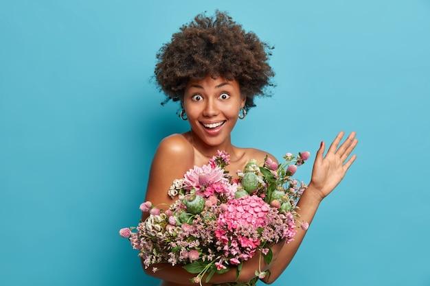 Gelukkig feest concept. aantrekkelijke chique jonge dame houdt boeket bloemen verhoogt palm blikken met opgewonden vrolijke uitdrukking