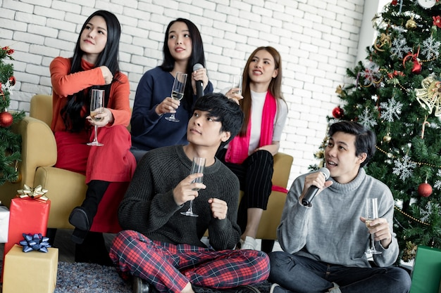 Gelukkig feest van jonge aziaten met wijn drinken en thuis een lied zingen tijdens het vieren van het kerstfestival. viering van het nieuwe jaar in huis. prettige kerstdagen en fijne feestdagen van bende tiener thai.