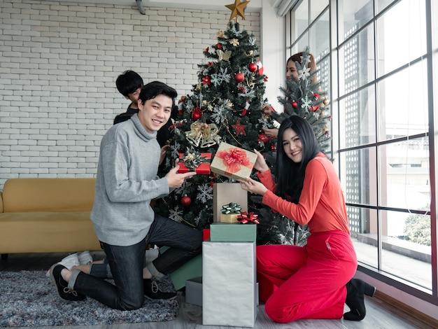 Gelukkig feest van jonge aziatische groep met geschenken thuis bij het vieren van het kerstfestival. thaise tieners vieren kerstmis en nieuwjaar. prettige kerstdagen en fijne feestdagen.