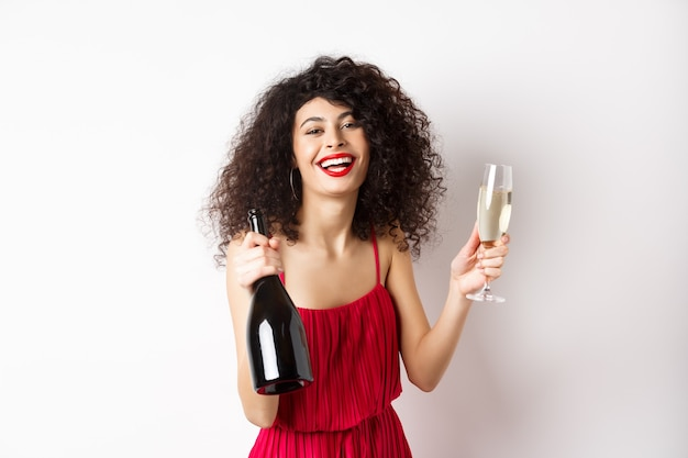 Gelukkig feest vrouw in rode jurk, lachen en houden fles champagne met glas, drinken en plezier hebben, vakantie vieren, staande op een witte achtergrond.