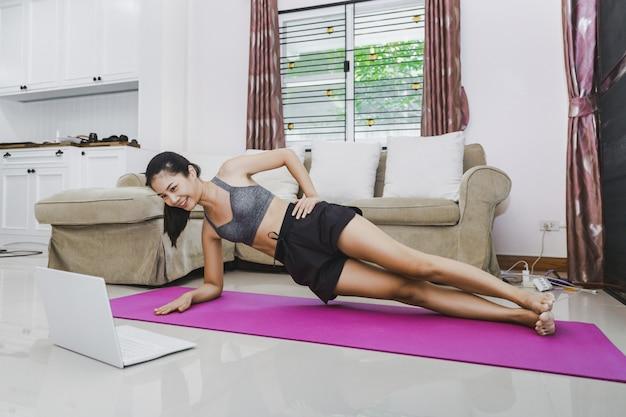 Gelukkig fit aziatische vrouw opleiding fitness oefening online met laptop thuis