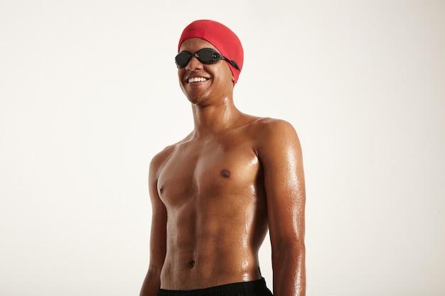 Gelukkig fit gespierde lachende afro-amerikaanse zwemmer met natte huid dragen rode pet en zwarte bril wegkijken