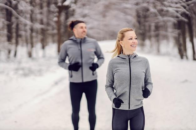Gelukkig fit sportvrouw haar vriend racen in de natuur op besneeuwde winterdag. samen fitnessen, buitenfitness, winterfitness