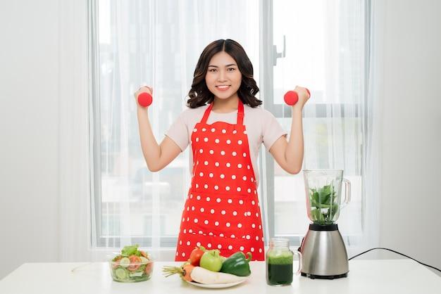 Gelukkig fitheid. aziatische vrouw met halters en vers drankje Premium Foto