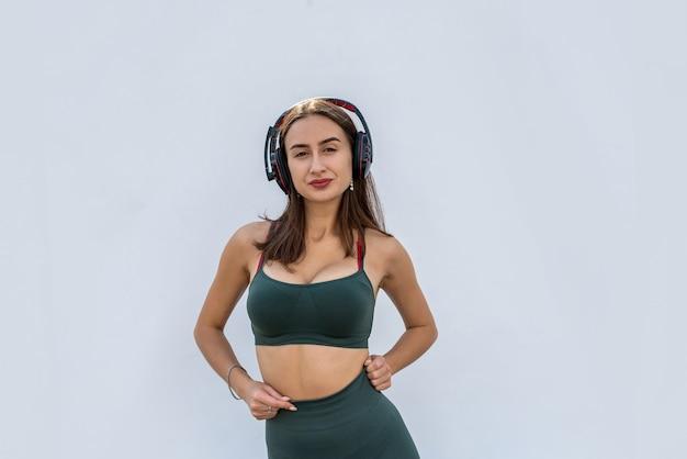 Gelukkig fitness vrouw in sportear luisteren naar muziek geïsoleerd. gezondheid levensstijl