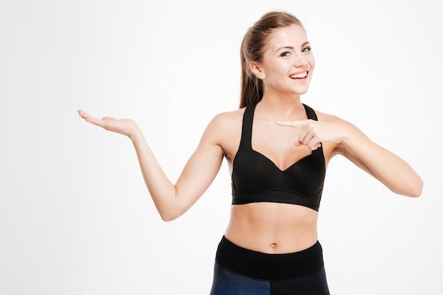 Gelukkig fitness vrouw wijzende vinger op copyspace op haar palm geïsoleerd