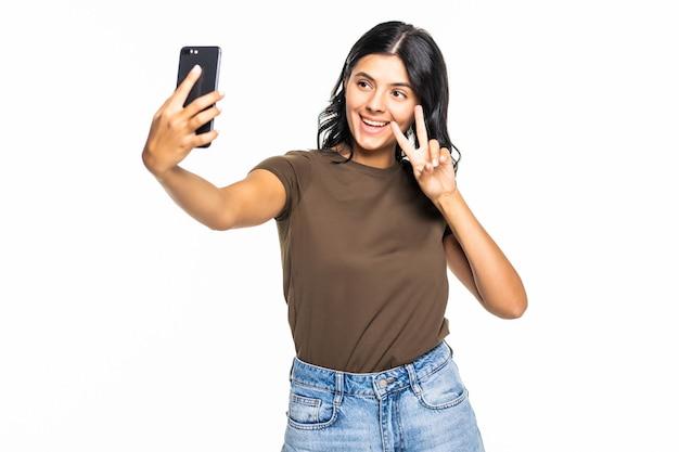 Gelukkig flirtend jong meisje dat foto's van zichzelf maakt op een smartphone, over een witte muur