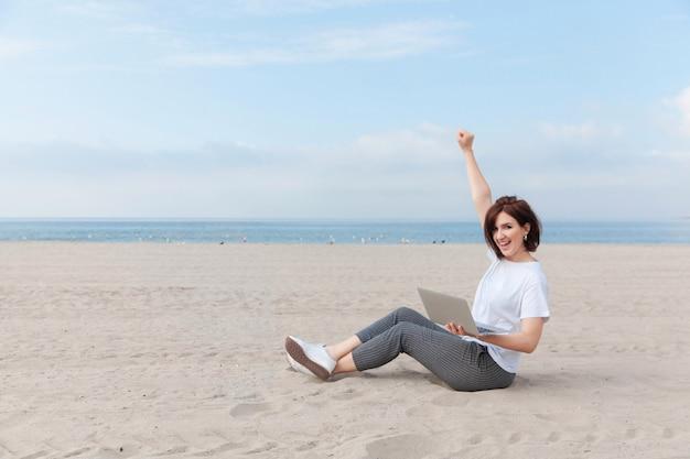 Gelukkig freelance vrouw hief haar handen op terwijl ze op het lege strand zat