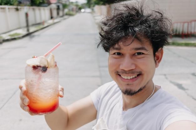 Gelukkig funky haar man drinkt italiaanse frisdranksiroop in hete zonnige straat van de zomer