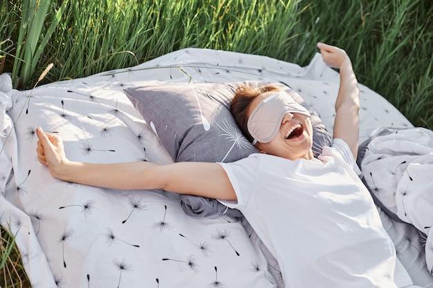 Gelukkig gapende vrouw met een slaapplooi en een wit casual t-shirt met strekkende armen als ze 's ochtends wakker wordt in bed in een groene weide, ontspannen en slapen buiten in het veld.
