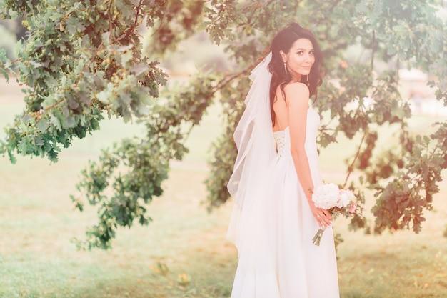Gelukkig gebruinde bruid in mooie witte jurk poseren met boeket bloemen in zonnige dag.