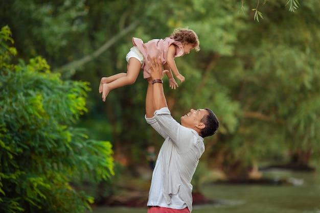 Gelukkig gebruinde mannelijke vader voor een wandeling met zijn kind. vader gooit zijn dochtertje over, ze spelen en lachen