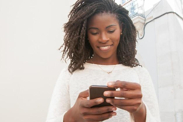 Gelukkig geconcentreerd zwart meisje dat online babbelt
