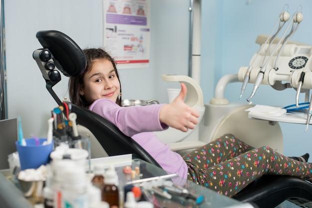 Gelukkig geduldig meisje die duimen tonen op tandkantoor. geneeskunde, stomatologie en gezondheidszorg concept