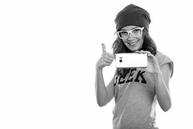 Gelukkig geekmeisje dat lacht terwijl ze een foto maakt met mobiele telefoon en duim opgeeft