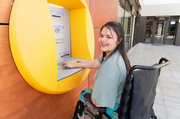 Gelukkig gehandicapte gehandicapte vrouw in rolstoel met behulp van atm-geldautomaat en glimlachend in de camera op zonnige zomerdag