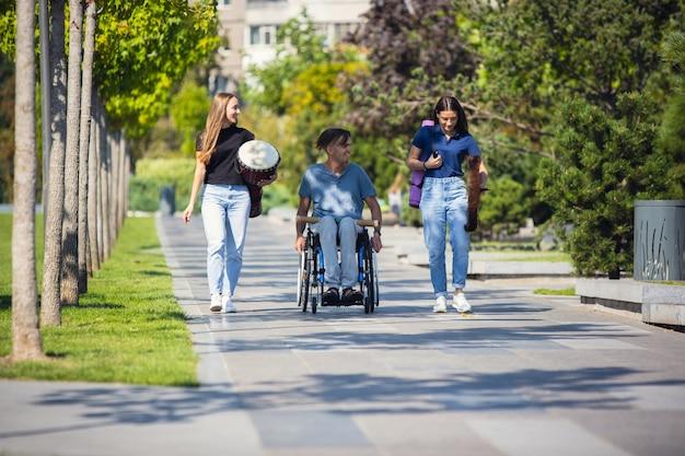 Gelukkig gehandicapte man in een rolstoel tijd doorbrengen met vrienden die live instrumentale muziek buiten spelen.