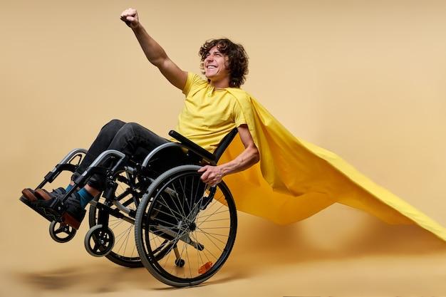 Gelukkig gehandicapte man in gele mantel doen alsof ze superheld zijn, handen opsteken. geïsoleerd in studio op beige achtergrond. wees gelukkig en sterk ondanks de moeilijkheden van het leven
