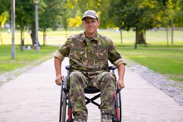 Gelukkig gehandicapte militaire man in rolstoel dragen camouflage uniform, verplaatsen op voetpad in stadspark. vooraanzicht. veteraan van oorlog of handicap concept