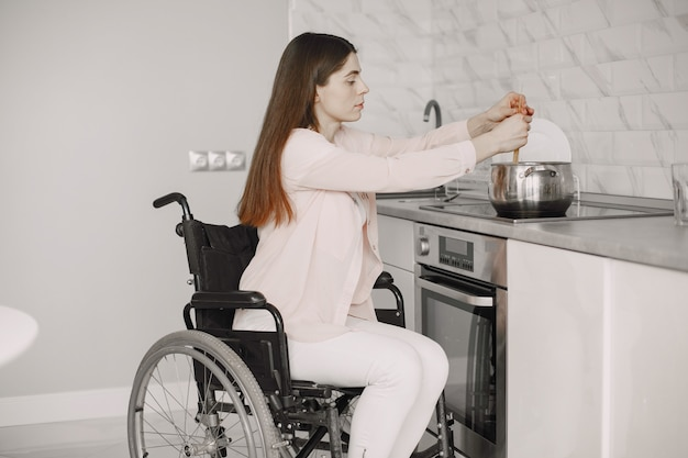 Gelukkig gehandicapte vrouw in rolstoel bereiden van voedsel in de keuken.