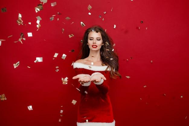 Gelukkig geïnspireerde jongedame die het nieuwe jaar viert met een glimlach studio-opname van brunette lachende vrouwelijke mo...