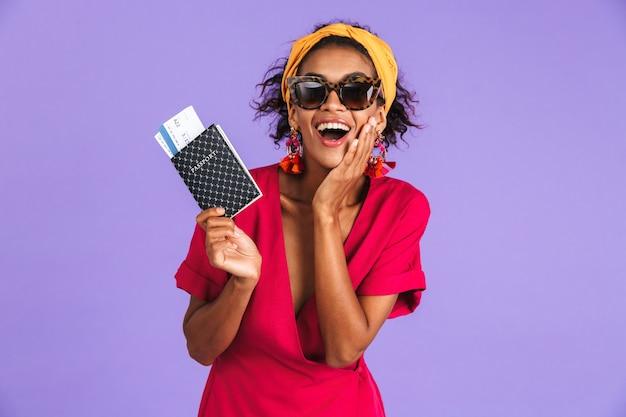 Gelukkig geïntrigeerde afrikaanse vrouw in jurk met paspoort met kaartjes