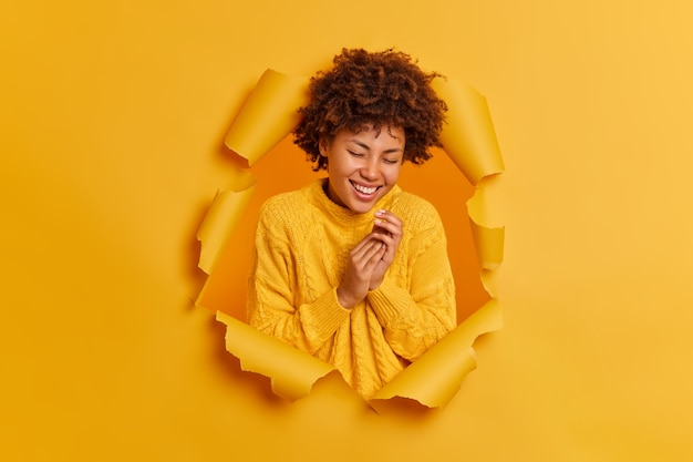 Gelukkig gekrulde afro-amerikaanse vrouw grijpt handen glimlacht breed en lacht positief