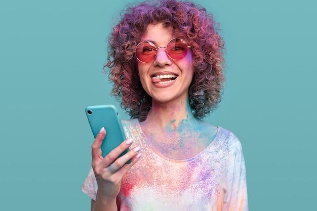 Gelukkig gekrulde haired vrouw met holi-kleuren met behulp van smartphone