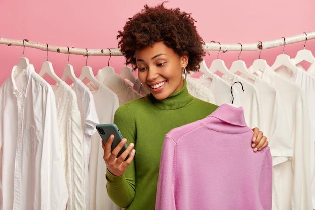 Gelukkig gekrulde harige vrouw kiest kleding, houdt comfortabele trui op hangers, witte outfits op rekken op achtergrond, berichten via mobiele telefoon.