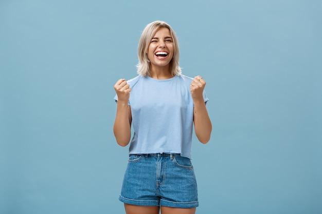 Gelukkig gelukkig meisje triomfen en lachen van geluk winnende eerste plaats gebalde vuisten in succesgebaar