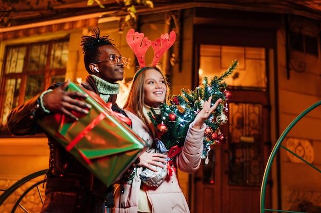 Gelukkig gemaskerd paar wandelen in de stad met geschenken en kerstboom