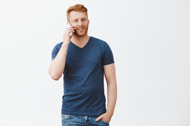 Gelukkig gember man met mobiele telefoon in de buurt van oor, opzij kijken, hand in zak houden