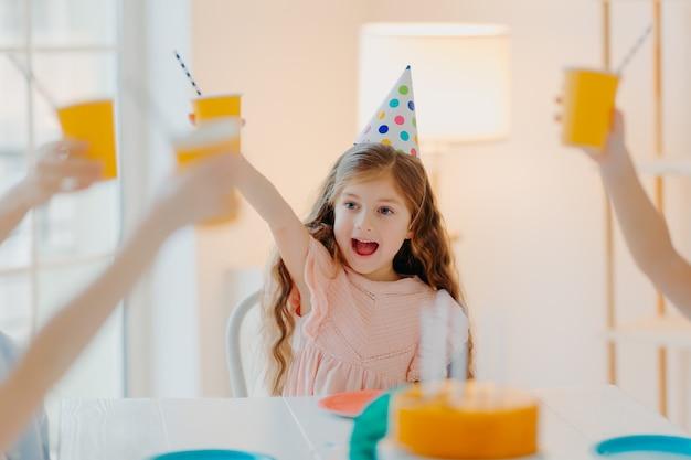 Gelukkig gembermeisje draagt feestmutsen, gerinkelbekers met drankje, heeft plezier met vrienden, viert samen verjaardag