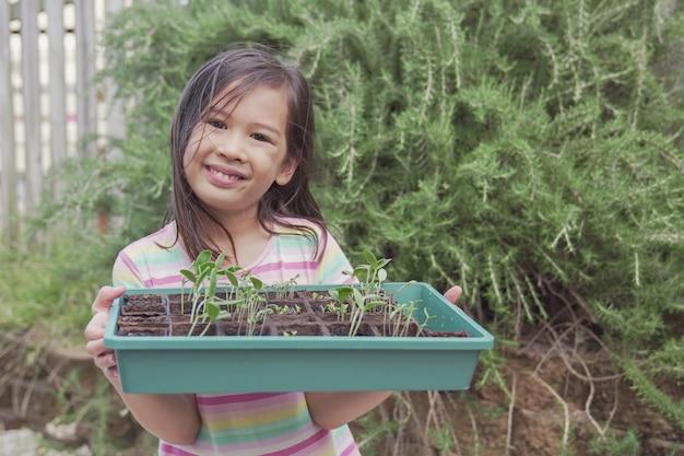 Gelukkig gemengd aziatisch de zaailingsdienblad van de meisjesholding, het plantaardige tuinieren, pret openluchtactiviteit, het duurzame leven, het sociale distantiëren concept