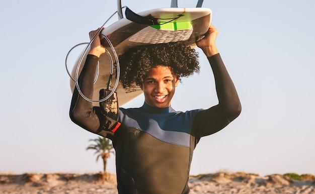 Gelukkig gemengd ras surfer jongen balanceren een surfplank op zijn hoofd. direct kijken naar de camera en glimlachen.