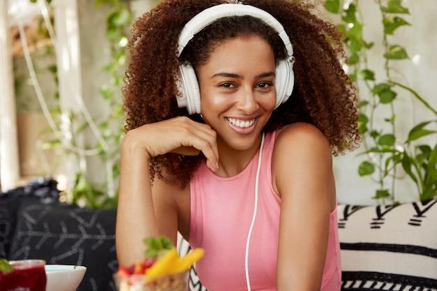 Gelukkig gemengd ras tienermeisje met krullend kapsel blij om te luisteren naar muziek of radio in koptelefoon, heeft langverwachte vakanties, zit op comfortabele bank met dessert. vrouwelijke blogger houdt van melodie