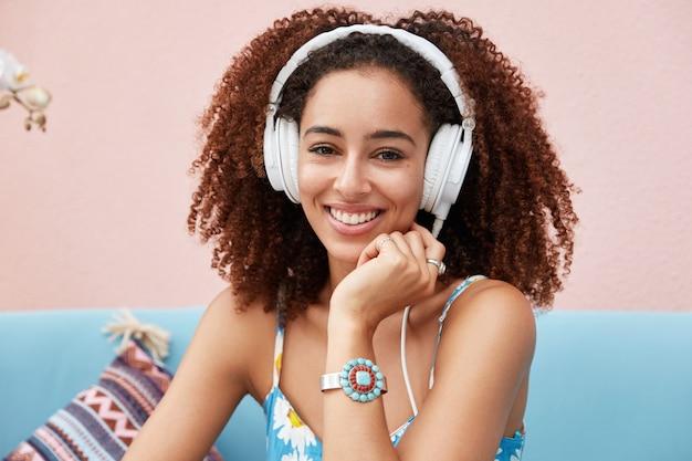 Gelukkig gemengd ras vrouwelijke blogger heeft een afro-kapsel, luistert naar favoriete radiostation in een koptelefoon of geniet van ontspanning met muziek